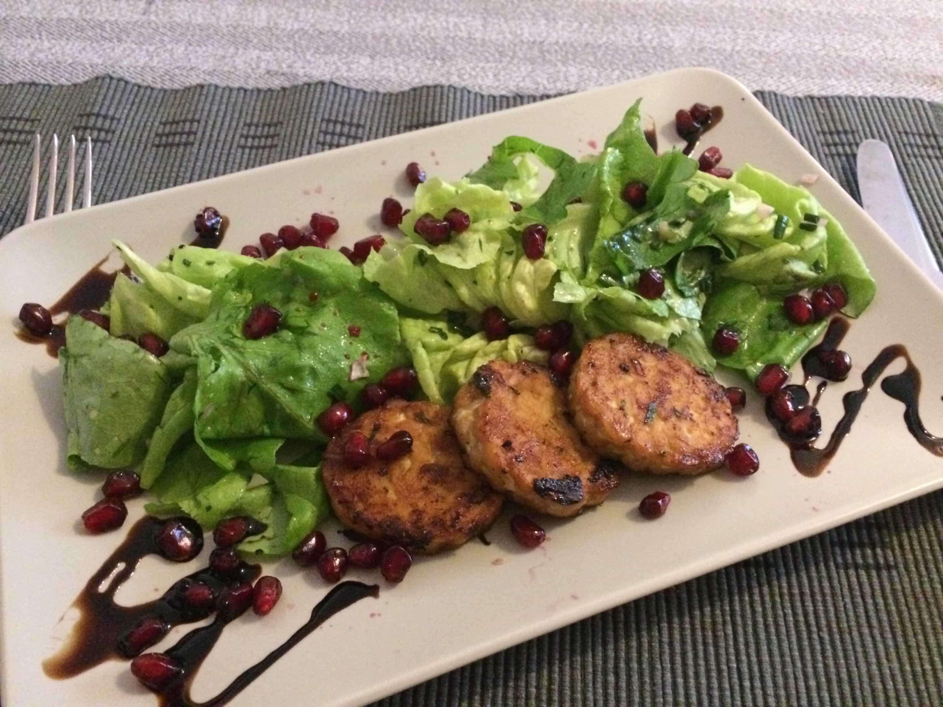 Salatteller mit marinierten Tempeh-Talern, Granatapfelkernen und Walnuss-Kräuter-Vinaigrette